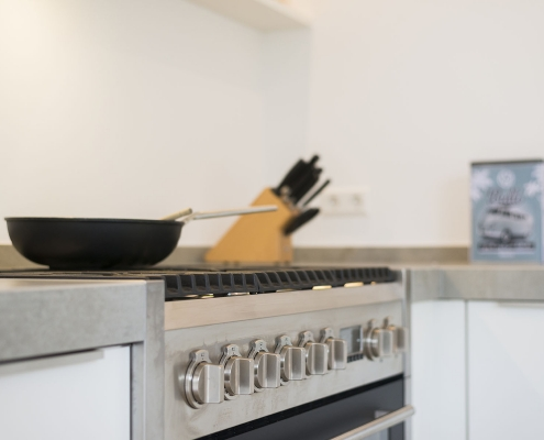 Strakke witte keuken met rvs grepen bij Zenner Keukens IJsselstein
